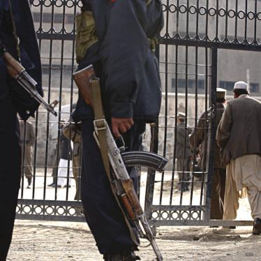 Officers stand guard in front of the Pul-e Charkhi prison's gate in Kabul
