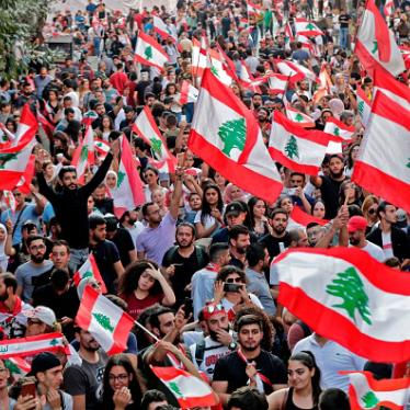Lebanese protesters wave national flags during demonstrations to demand better living conditions on October 21, 2019 in downtown Beirut.