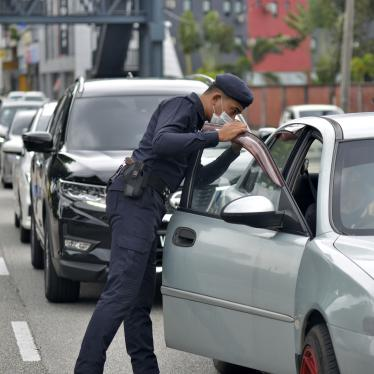 Police officers check vehicles at a roadblock to ensure that people abide by the movement control order in downtown Kuala Lumpur, Malaysia, March 19, 2020. © 2020 AP Photo